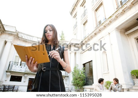 Attractive businesswoman standing in a luxury classic architecture coffee shop terrace, taking notes in her agenda while her colleagues are meeting behind her. - stock photo