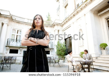 Attractive businesswoman standing in a luxury classic architecture coffee shop terrace, waiting with her arms crossed. - stock photo