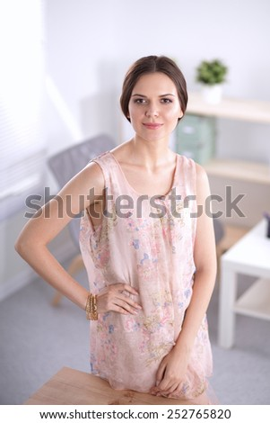 Attractive businesswoman standing  near desk in office - stock photo