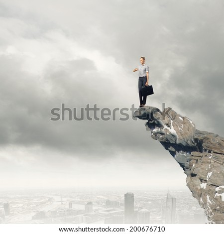 Attractive businesswoman standing on edge of mountain