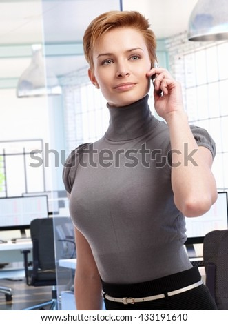 Attractive businesswoman talking on mobile phone at corporate office. - stock photo