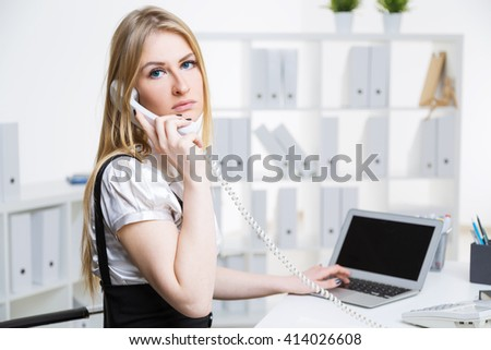 Attractive businesswoman talking on the phone at office desk with blank computer screen  - stock photo