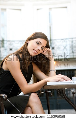 Attractive businesswoman using a laptop computer while sitting in a coffee shop, outdoors. - stock photo