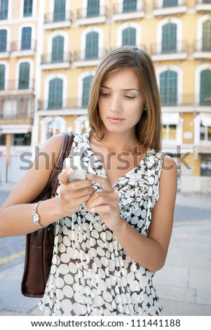 Attractive businesswoman using her cell phone outdoors, in a classic city center. - stock photo