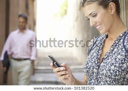 Attractive businesswoman using her cell phone outdoors, while a businessman walks by in the background.