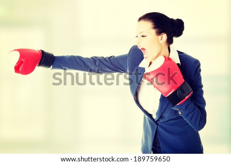 Attractive businesswoman with boxing gloves - fighting - stock photo