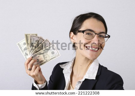 Attractive businesswoman with glasses holding cash earnings