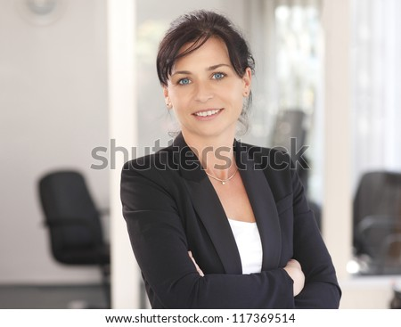 Attractive businesswoman with her arms crossed - stock photo