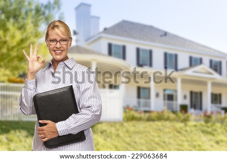 Attractive Businesswoman with Okay Hand Sign In Front of Nice Residential Home. - stock photo