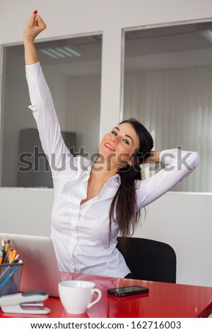 Attractive businesswoman with raised arms is very excited and celebrate the victory.