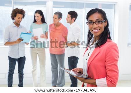 Attractive businesswoman with tablet pc in the office - stock photo