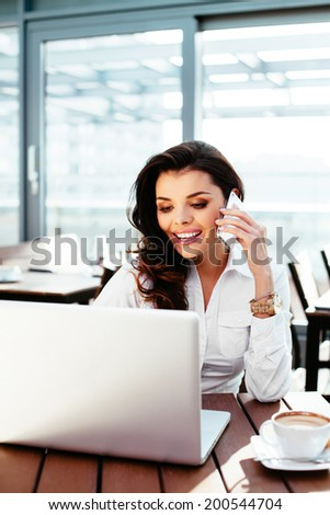 Attractive businesswoman working an her laptop and talking on the phone - stock photo
