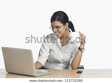 Attractive businesswoman working on a laptop and drinking coffee