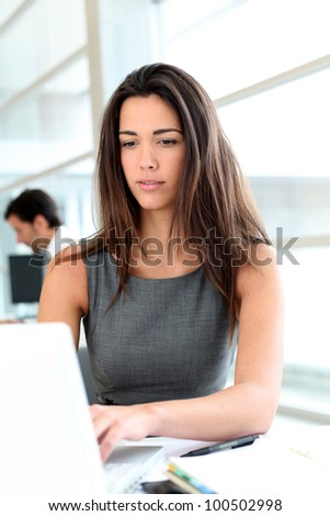 Attractive businesswoman working on laptop computer - stock photo