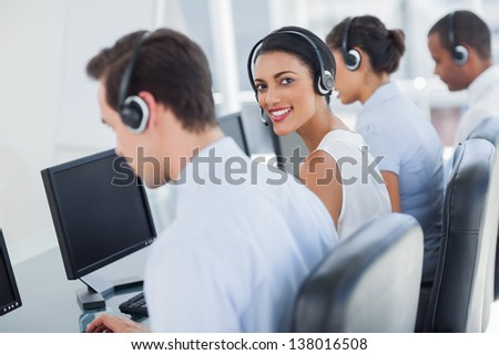 Attractive call centre employee looking over shoulder while wearing a headset