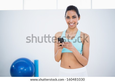 Attractive calm woman text messaging with her smartphone smiling at camera
