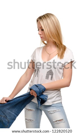 Attractive casual blonde girl with a lovely figure standing pulling a pair of blue denim jeans, studio portrait isolated on white - stock photo