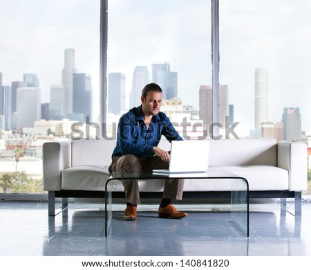 Attractive casual business man working in a Penthouse Suite with Los Angeles Skyline behind him - stock photo