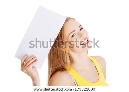 Attractive casual caucasian woman holds empty white piece of paper. Isolated on white. - stock photo
