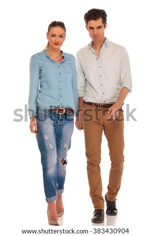 attractive casual couple walking in white isolated studio background holding hands while looking at the camera  - stock photo