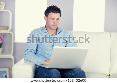 Attractive casual man sitting on couch using laptop in bright living room