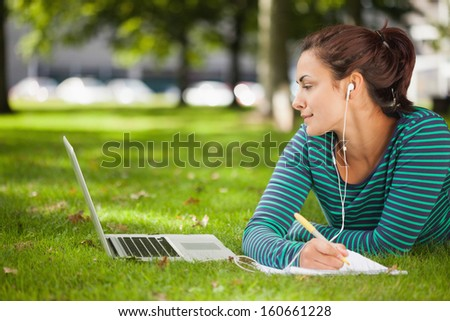 Attractive casual student lying on grass taking notes on campus at college - stock photo