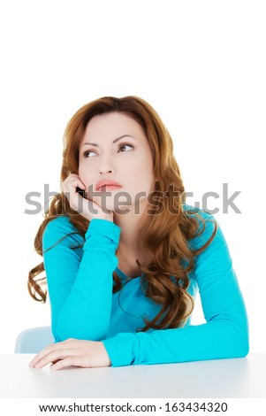 Attractive casual woman lsitting and looking up. Isolated on white. - stock photo