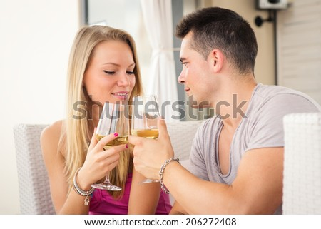 Attractive casual young couple drinking a glass of wine in a hotel terrace.