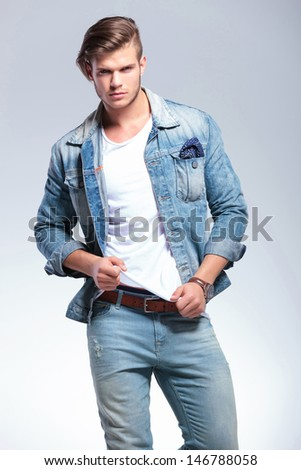 attractive casual young man pulling on his shirt while looking at the camera. on gray background - stock photo
