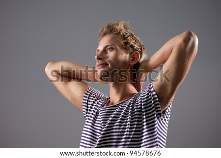Attractive caucasian blond young adult  in relaxed pose isolated on grey background - stock photo