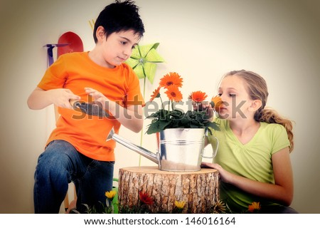 Attractive Caucasian boy and girl with flowers, tools, garden supplies.  Studio Portrait. - stock photo