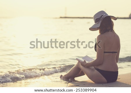 Attractive Caucasian brunette woman in bikini reading a book on the shore of a beach at sunset - stock photo