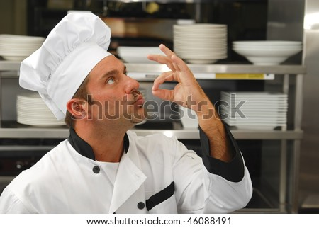 Attractive Caucasian chef kissing his fingers to show how tasty the food is. - stock photo