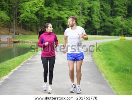 Attractive caucasian couple friends running in park. - stock photo