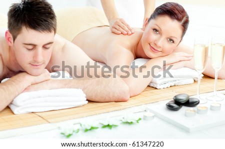 Attractive caucasian couple receiving a back massage in a spa center - stock photo