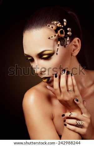 Attractive caucasian female studio portrait with spider on her face - stock photo