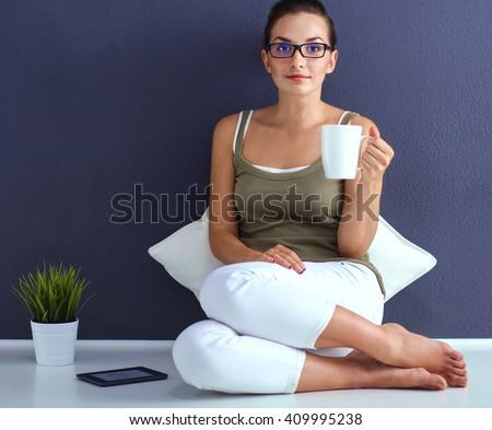 Attractive caucasian girl sitting on floor - stock photo