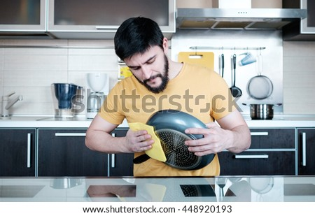 Attractive caucasian man cleaning the dripping pan in the kitchen