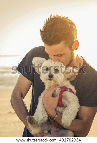 Attractive caucasian man is kissing his dog at the beach - concept about animals, people and lifestyle - stock photo