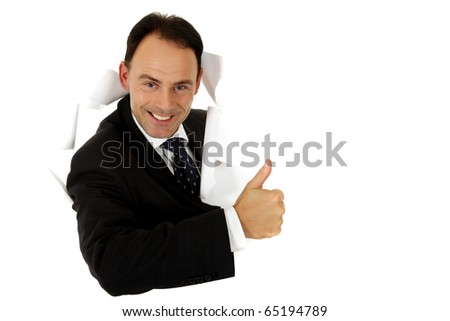 Attractive caucasian middle aged businessman breaking through a paper wall showing thumb up. Happy face. Studio shot. White background