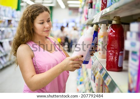 Attractive Caucasian woman choosing conditioner for washing in shop - stock photo