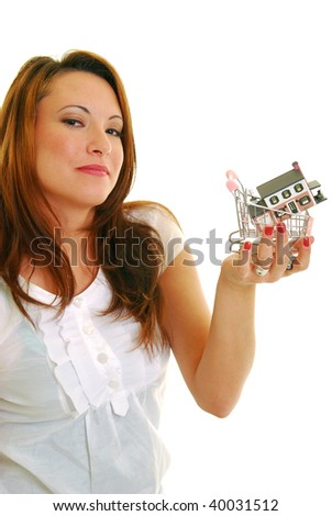 Attractive Caucasian woman holding miniature shopping cart with a house in it.