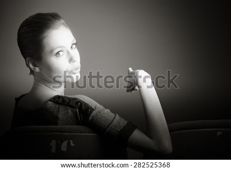 Attractive caucasian woman in the theatre in her 30 isolated on a grey background, black and white image