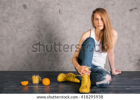 Attractive caucasian woman in yellow boots sitting on wooden surface with orange juice and fruit on concrete wall background - stock photo