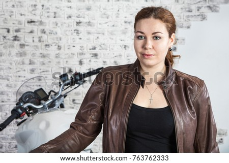 Attractive Caucasian woman motorcyclist portrait. Brown leather jacket and motorbike behind, indoors