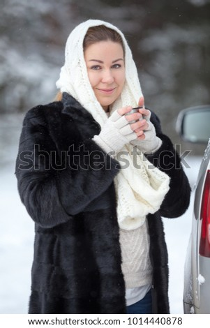 Attractive Caucasian woman warming with hot tea mug while standing with unbutton fur coat in white woollen scarf at winter season