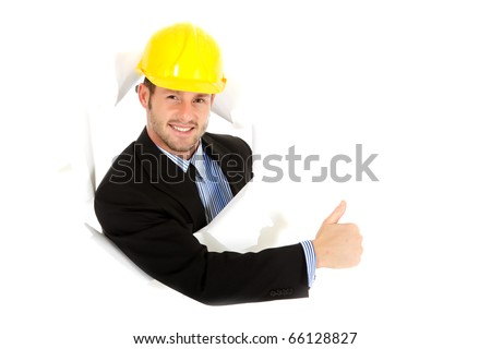 Attractive caucasian young businessman with protective helmet breaking through a paper wall showing thumb up. Happy face. Studio shot. White background - stock photo