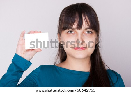 Attractive caucasion girl with business or gift card. Selective focus. Space for text available. - stock photo