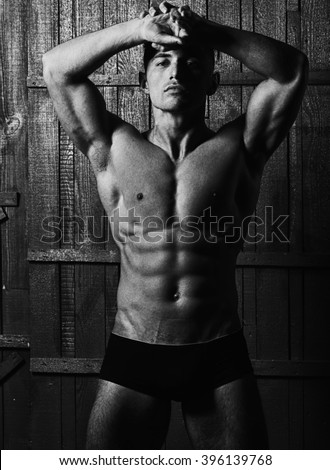 Attractive charming muscular athlete young man in fashion male trunks with athletic perfect beautiful bare body  standing with hands on head on wooden background black and white studio, vertical  - stock photo