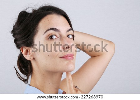 Attractive charming young woman turning and smiling at the camera with her hand to her long dark hair tied neatly above her head, over grey - stock photo